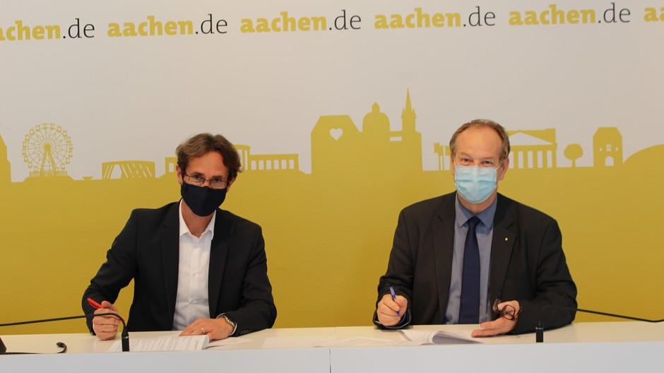 Lehrer Olaf Grodde (l.) und Stadtarchäologe Andreas Schaub (r.) bei der Unterzeichnung des Vertrages.