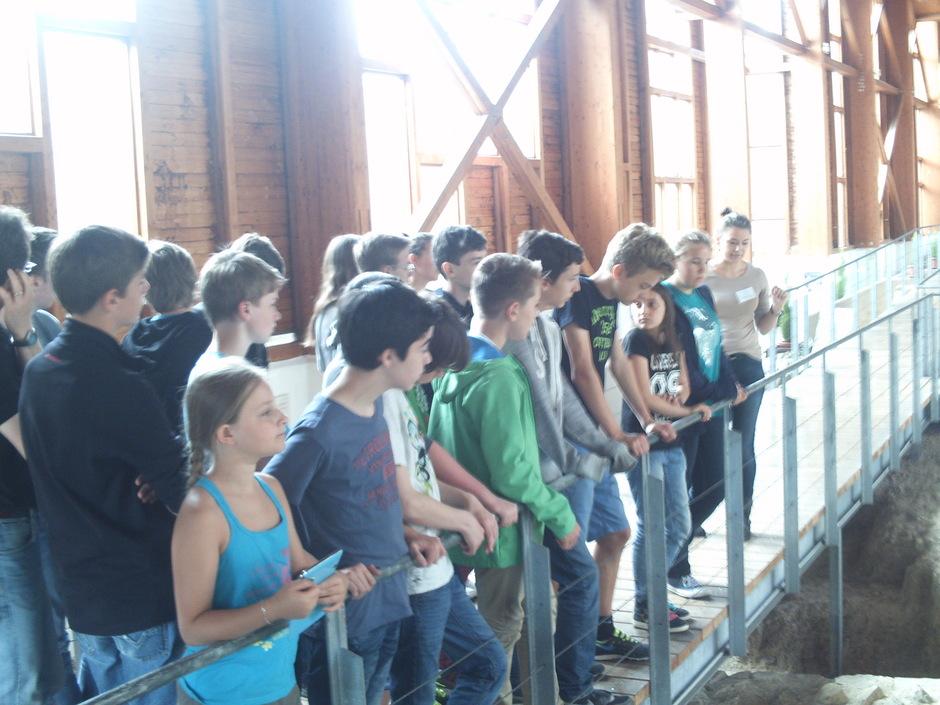 Schüler der Archäologie lauschen der Führung auf der Porticus der Römervilla.