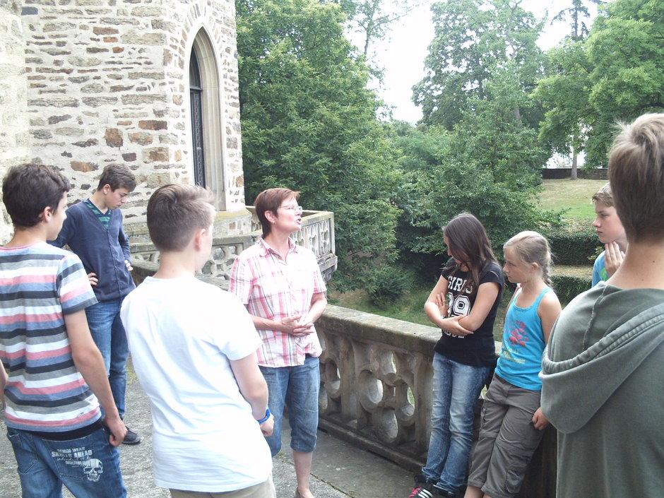 Frau Menacher führt Schüler der Archäologie-AG durch das Museum.