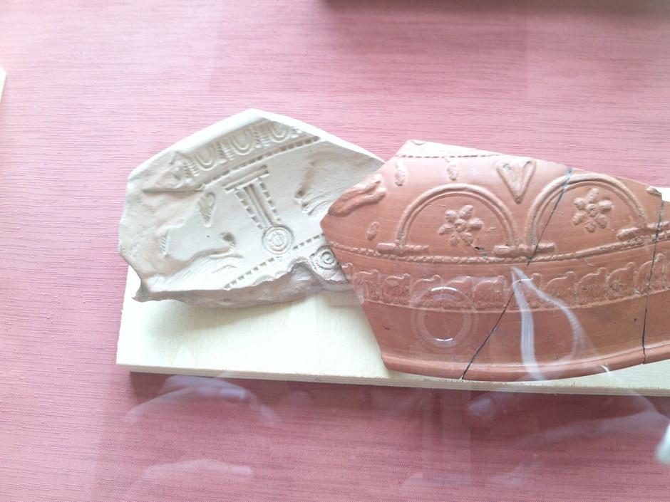 Links sieht man die Scherbe einer sogenannten Punze, mit der die Verzierungen auf die Terra-Sigillata-Gefäße aufgedrückt wurden.
