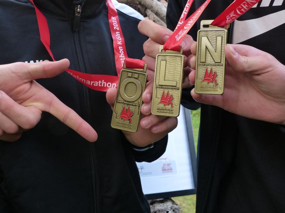 Die Siegermedaillen des Schul-Staffelmarathons us der Stadt mit K.