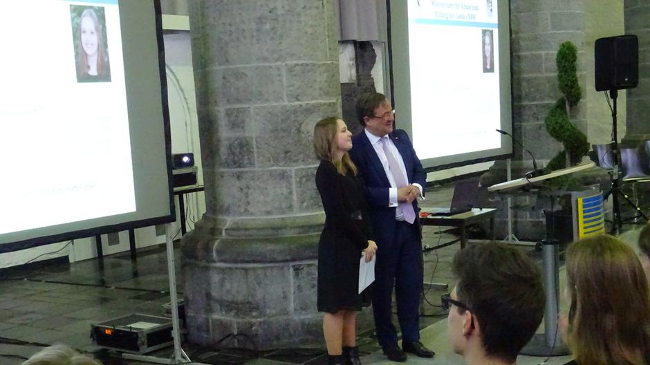 Die Preisträgerin Martha Birken und Ministerpräsident Armin Laschet strahlen in Kameras der Medienvertreter