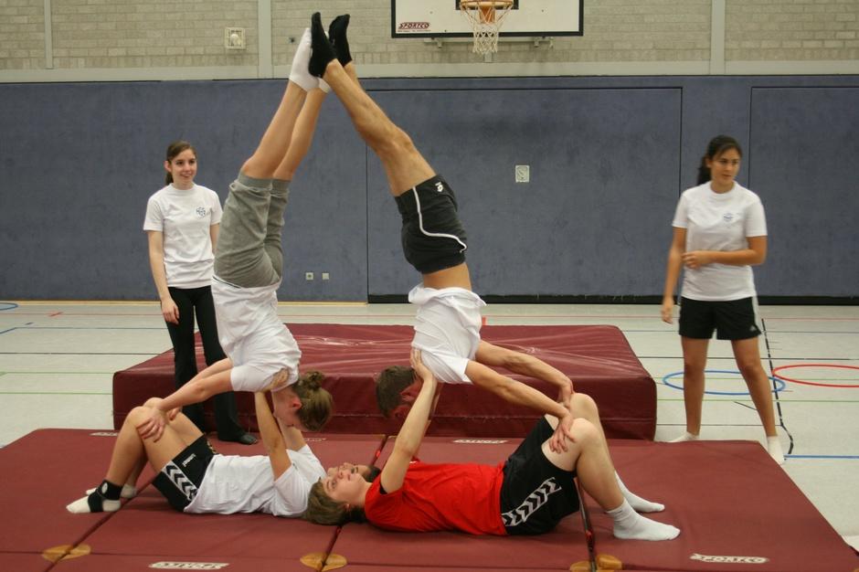 Körperspannung, Konzentration und viel Vertrauen: Schülerinnen und Schüler der Akrobatik AG beim Einstudieren von Figuren auf den Matten in unserer großen Turnhalle