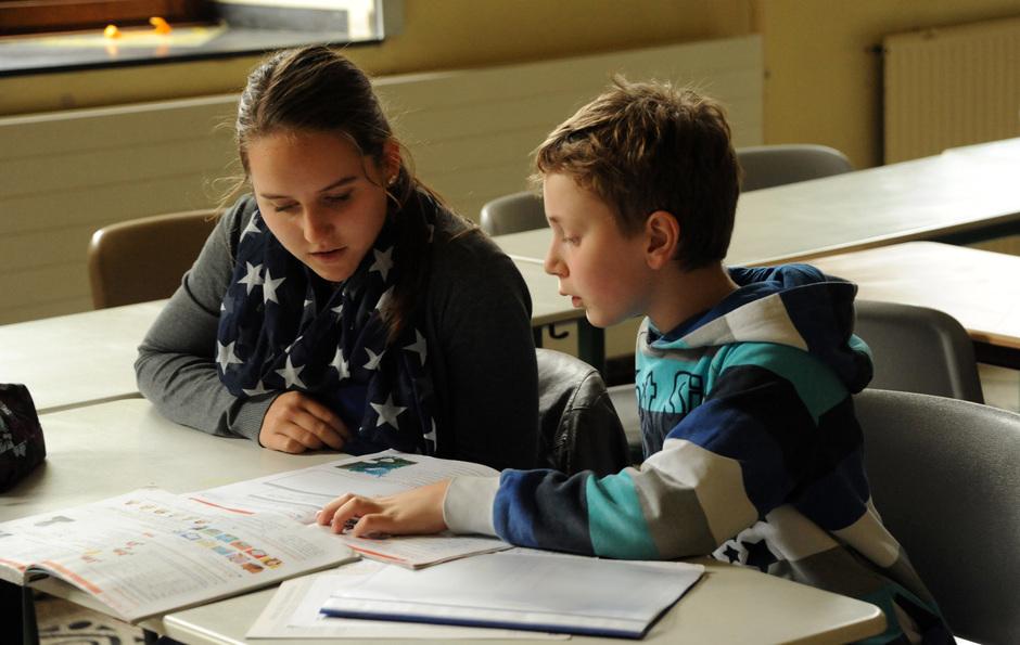 """Unterstufenschüler Pascal zeigt Oberstufenschülerin Mara, was in Englisch für die nächste Klassenarbeit ansteht. """"Schüler helfen Schülern"""" - die Zusammenarbeit zwischen älteren und jüngeren Schülern macht Freude und bringt Gewinn."""