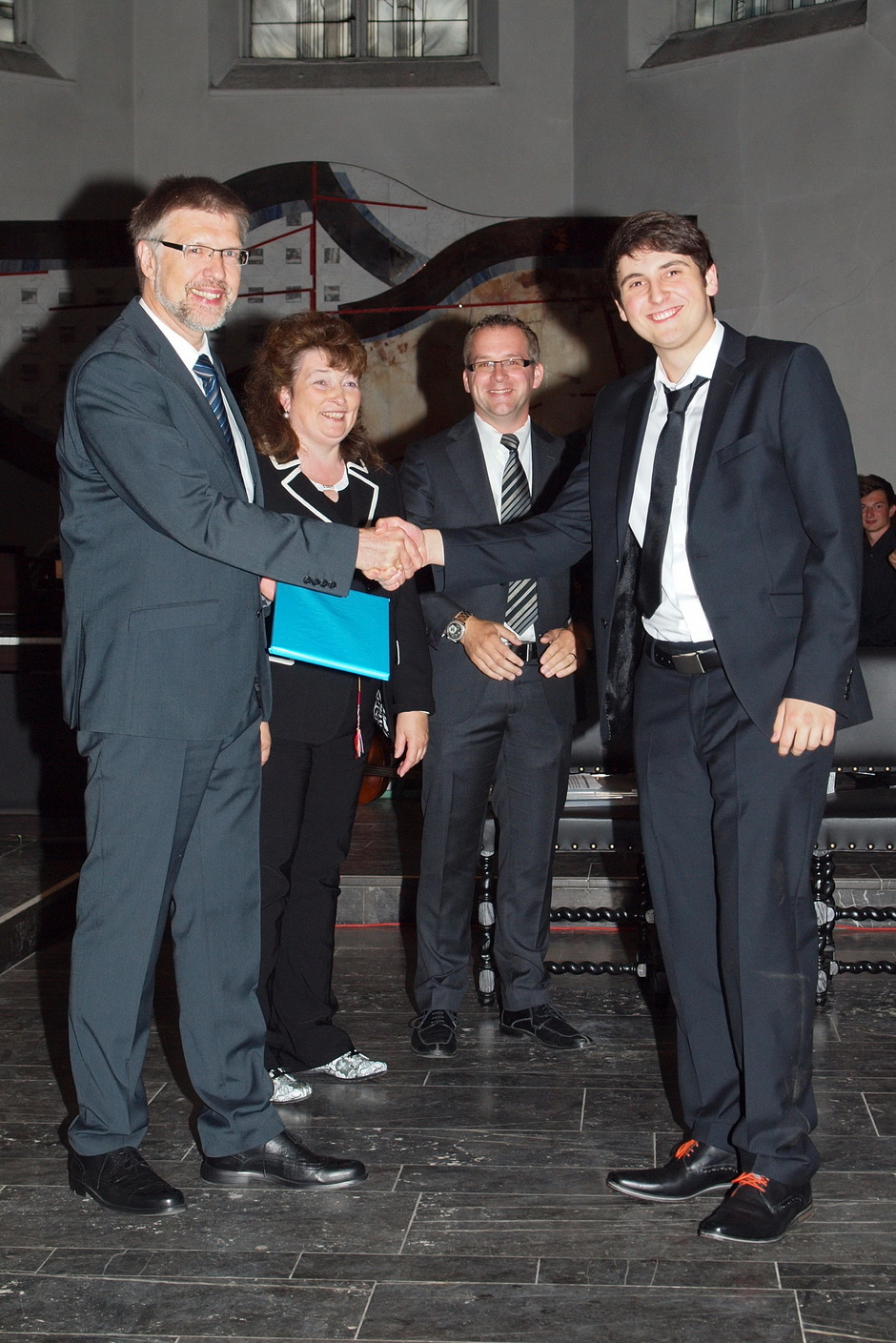 Das Ziel erreicht: Bei der Abiturfeier überreicht Schulleiter Christoph Barbier das Abiturzeugnis. Den Tutoren steht die Freude ins Gesicht geschrieben, unserem Abiturient der ganze Stolz. Gratulation und zugleich ein festes Versprechen: Wir bleiben über das HGG miteinander verbunden!