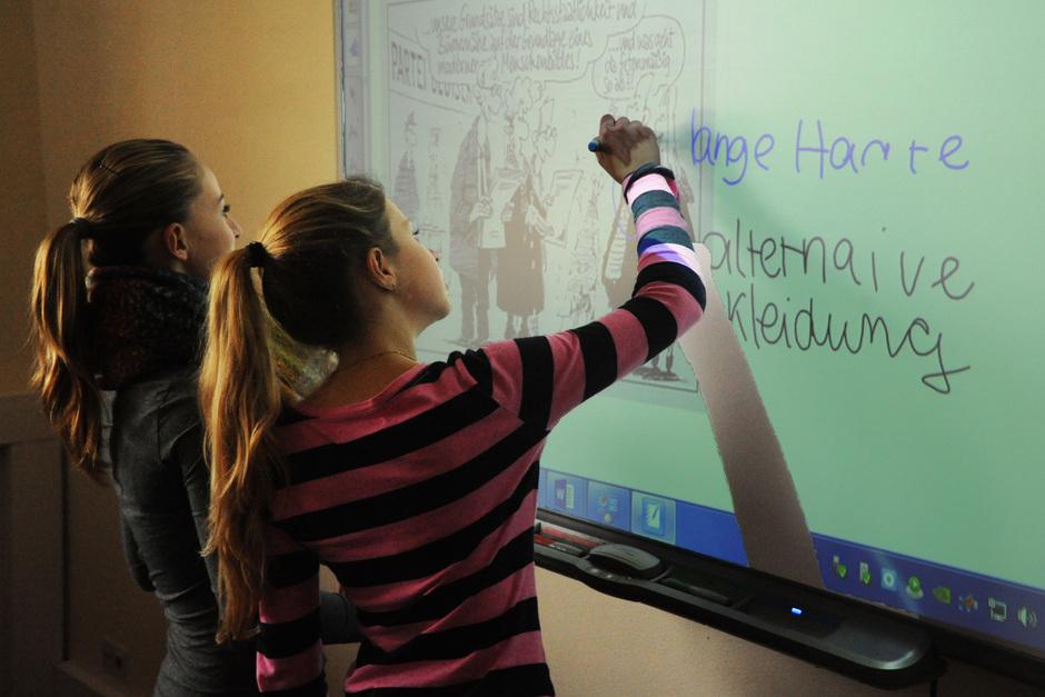 Raquel und Lynn arbeiten an der politischen Karikatur am Smartboard. Die elektronische Tafel hilft den Unterricht anschaulicher und aktueller zu gestalten.